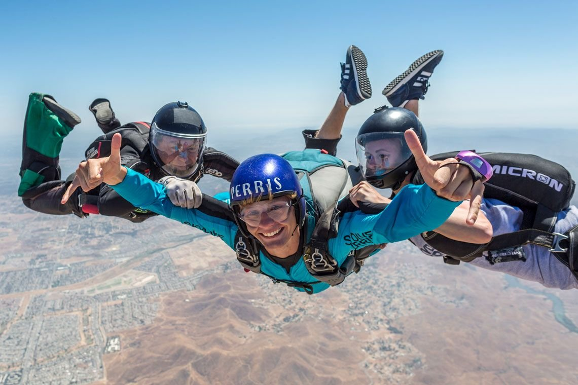 first time AFF skydiving student in freefall with 2 skydiving instructors