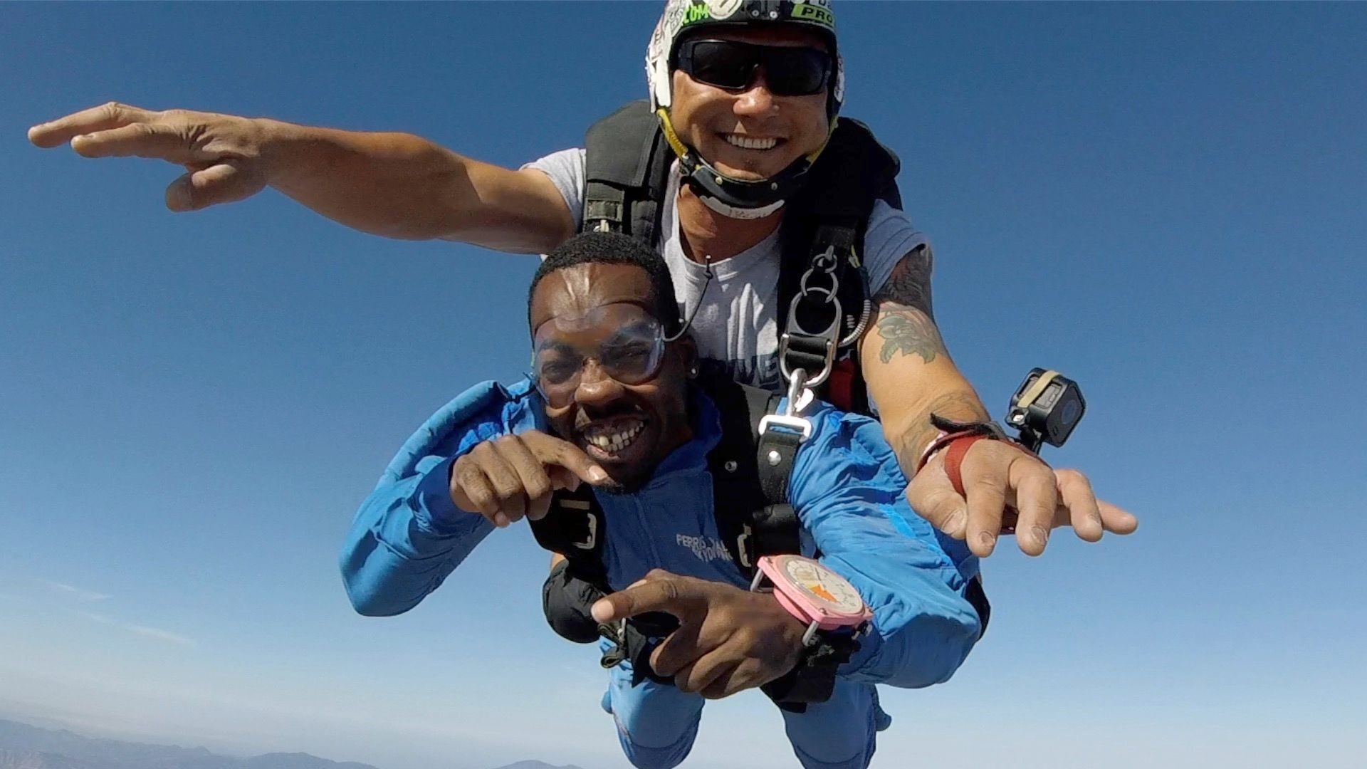 first time skydiving student points at camera in freefall