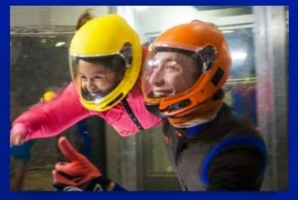 young girl tries indoor skydiving with instructor by her side